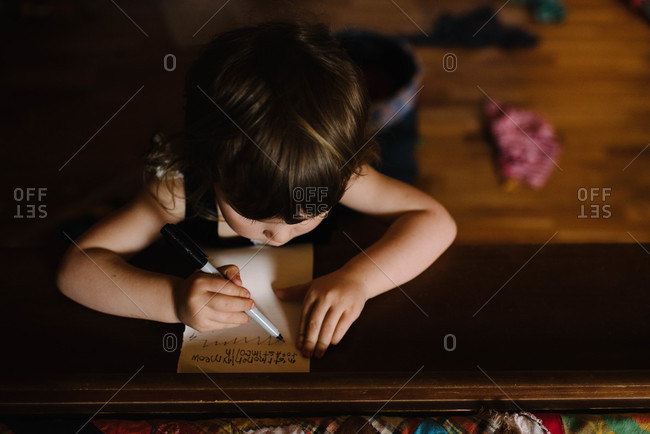 Young girl writing at a table