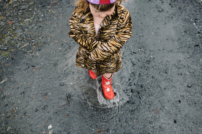 Little girl in red boots standing in a puddle