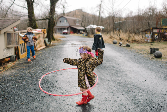 Young girl hula hooping on a road