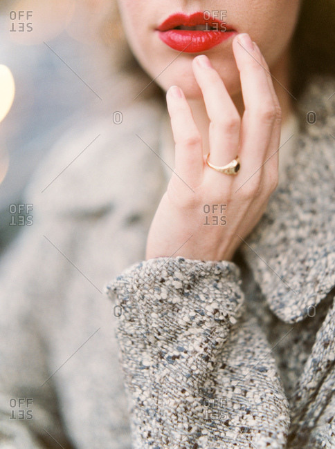 Young woman touching her red lips