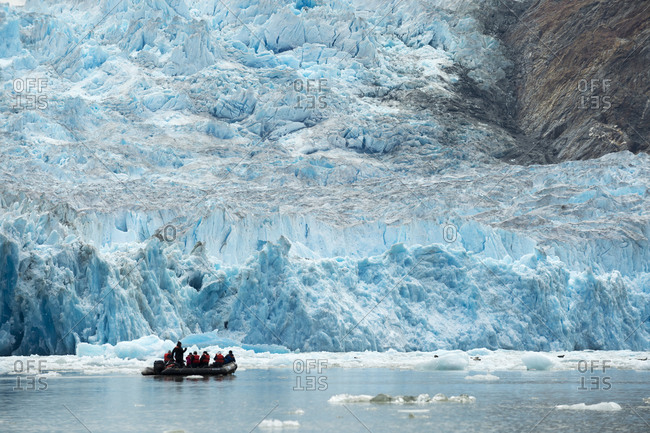 Small inflatable boat carrying tourists close to the South Sawyer Glacier, Tracy Arm fjord, Alaska