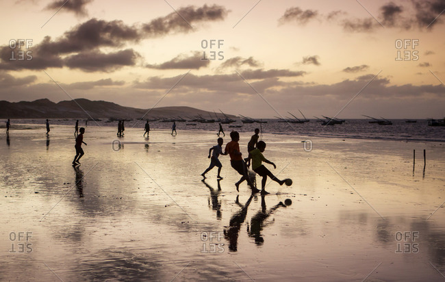A group of young boys play soccer on a beach at sunset in Ceara state, Brazil