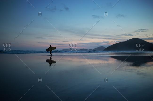 A surfer on the beach at dusk in Itamambuca, Ubatuba, Brazil