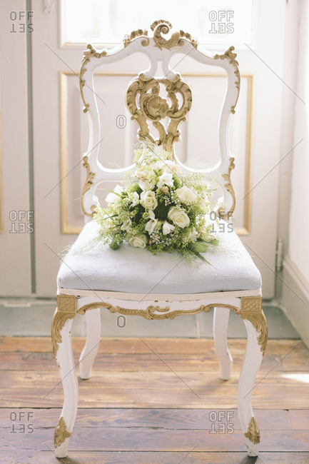 A bouquet of flowers on a decorative chair