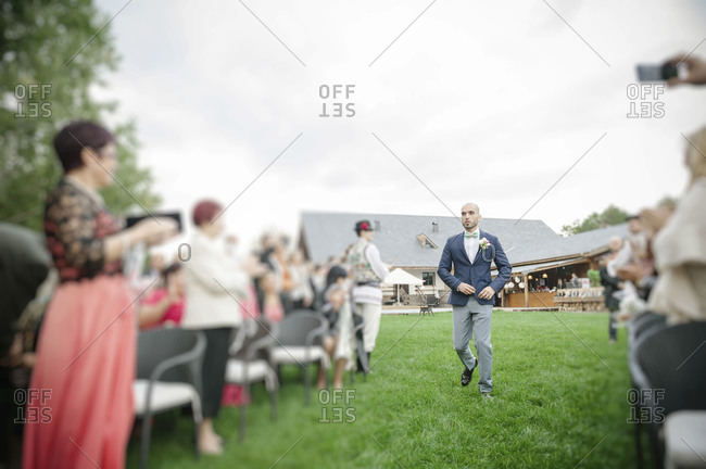 A groom walks down the aisle at an outdoor wedding