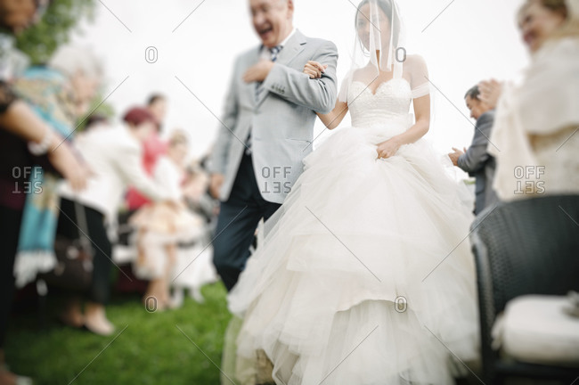 A father walks his daughter down the aisle at a wedding