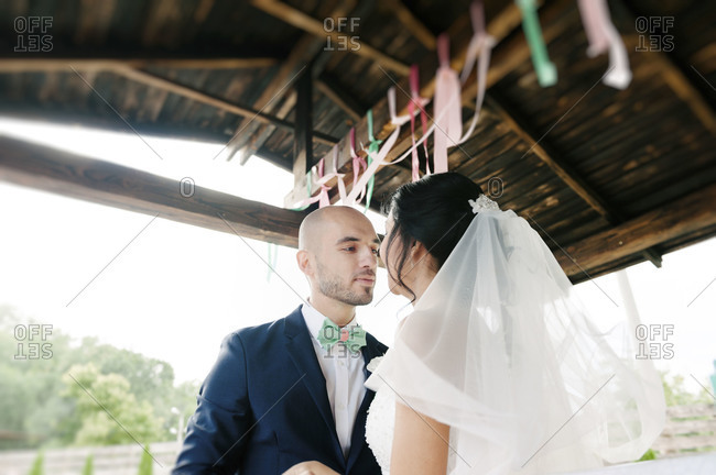 A groom leans in to kiss his bride at a wedding