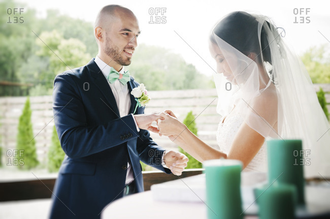 A bride and groom exchange rings at a wedding