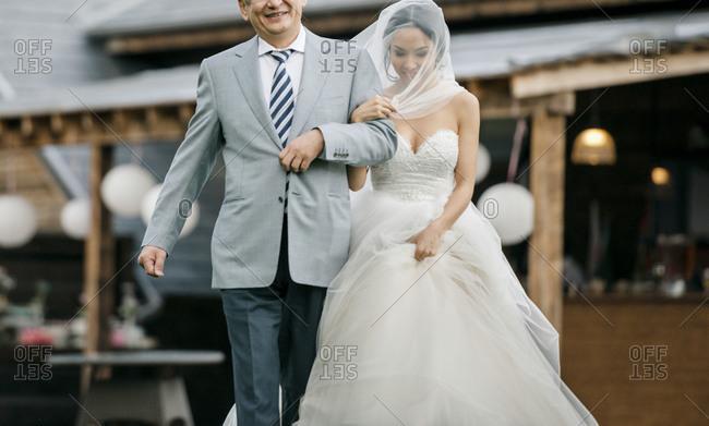 A man walks his daughter down the aisle at a wedding