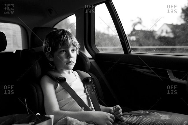 Young boy with a book riding in a car seat