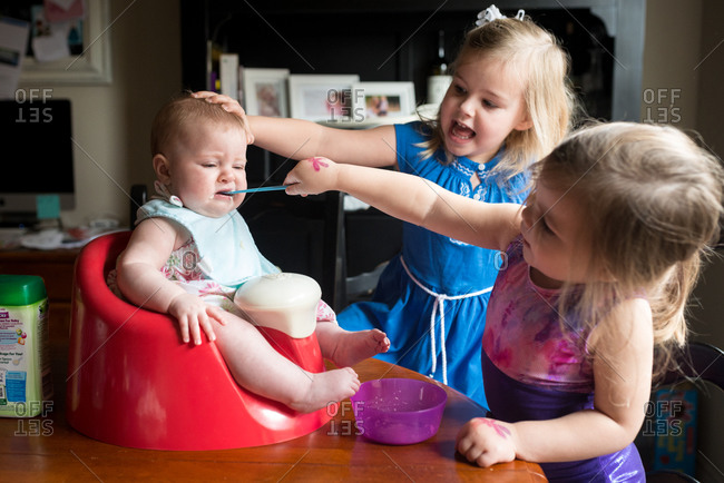 Two little girls feeding young infant solid food