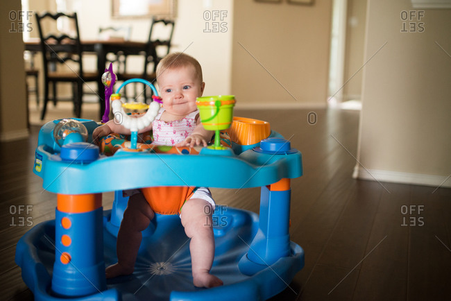 Infant in activity center in house