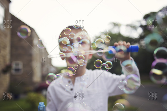Boy blowing bubbles outdoors