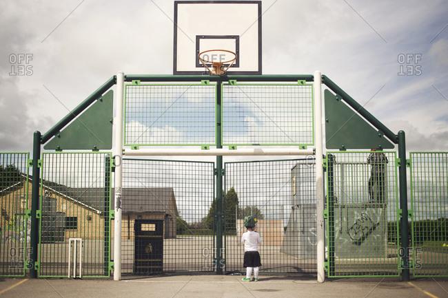 Little boy in a green helmet watching older kids in fenced skate park