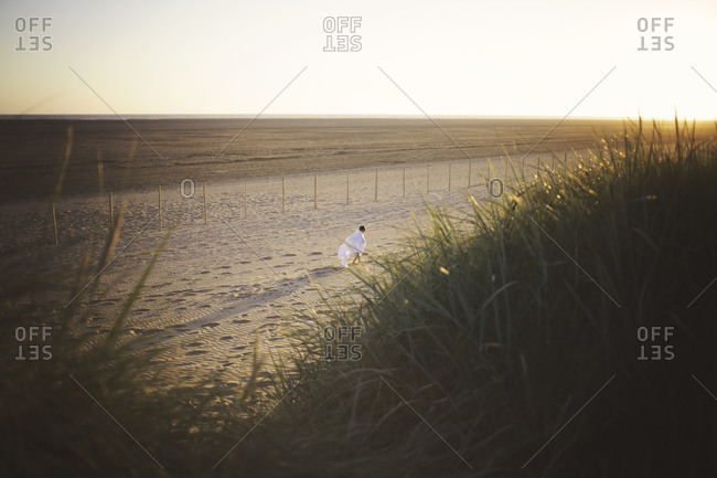 Young boy wrapped in a white blanket walks on a beach at dusk