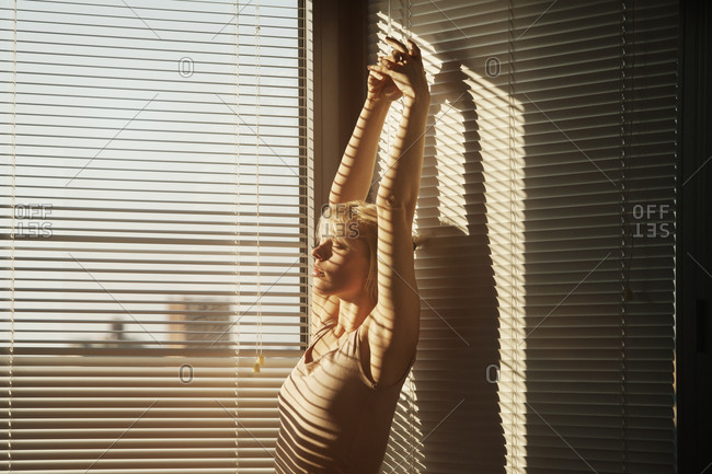Woman Stretching In The Sunlight Coming Through Window Blinds