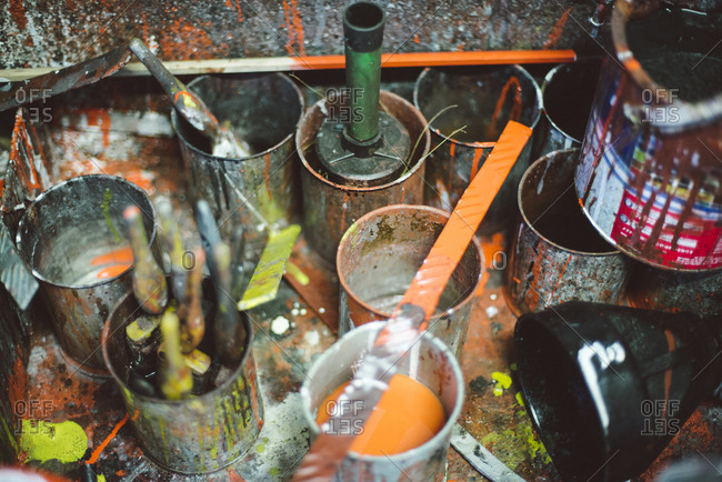 Messy paint cans and brushes in workshop
