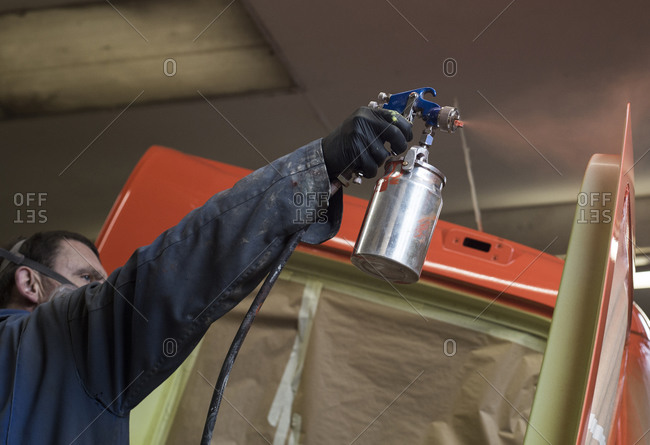 Man spray painting a vehicle in workshop