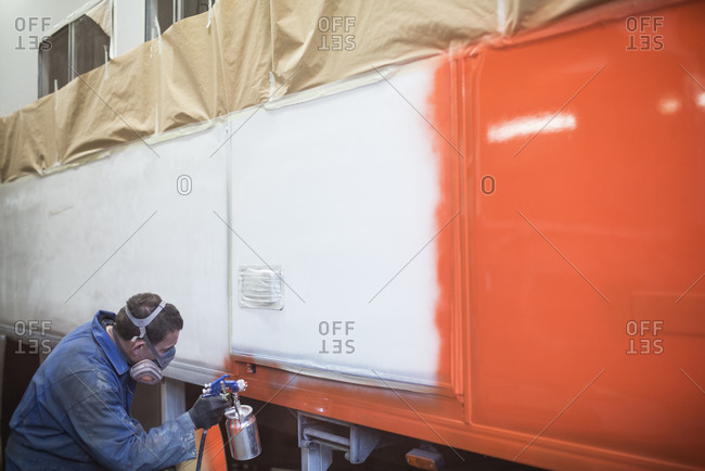Man spray painting a large vehicle in workshop