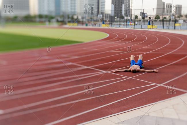 Dubai, UAE - April 10, 2014: Runner lying sprawled out on track