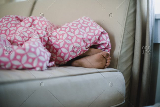 Kid's dirty feet sticking out of blanket