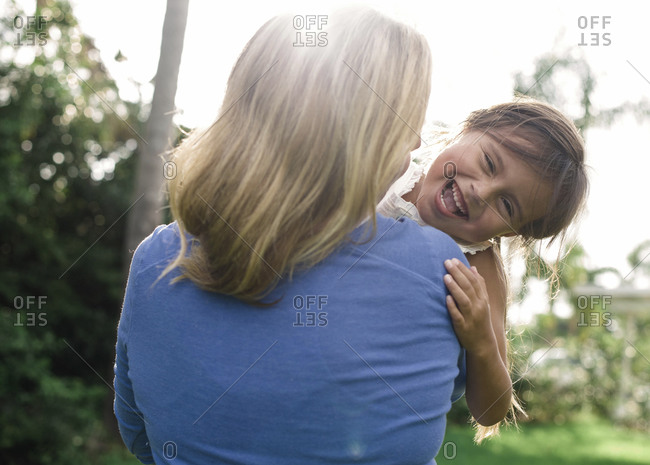 Mom carrying giggling daughter outside