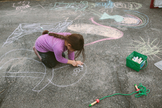 Girl drawing on concrete with sidewalk chalk
