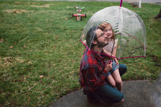 Dad and daughter looking up while underneath umbrella in rain