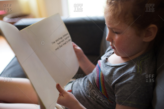 Young girl reading book on couch at home