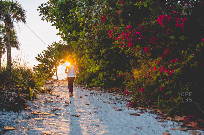 Girl walking on beach path at sunset