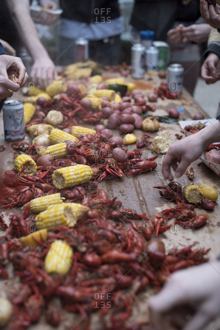 Hands pick over a table full of crayfish and corn
