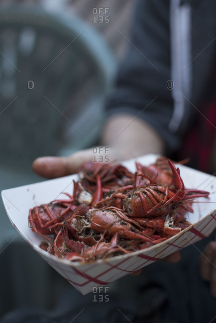 Person holding up tray of crayfish