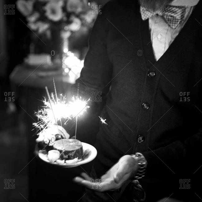 Man holds birthday cake with sparklers