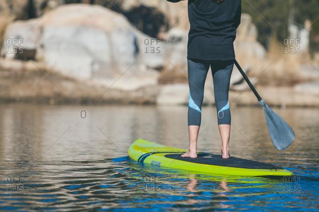 Legs of standup paddler, Boulder Bay, Big Bear Lake, California