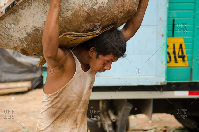 July 15, 2012: Young man carrying garbage during clean up in Peru