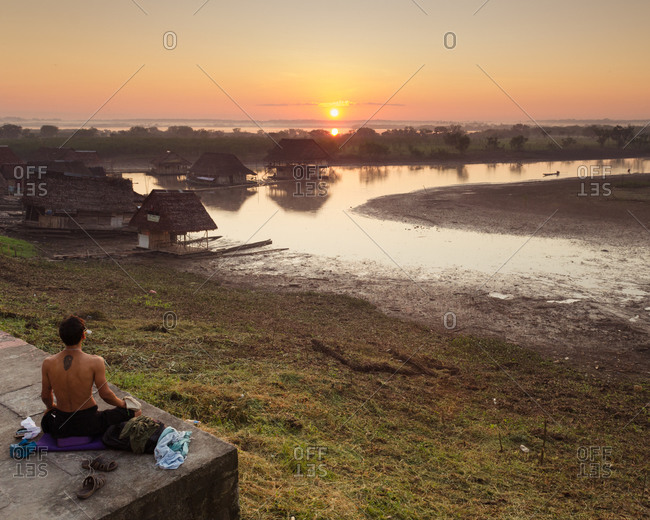 Man sitting watching peaceful sunset over Amazon