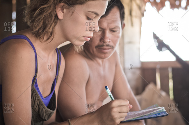 August 8, 2012: Young humanitarian aid worker with Peruvian man writing in notebook