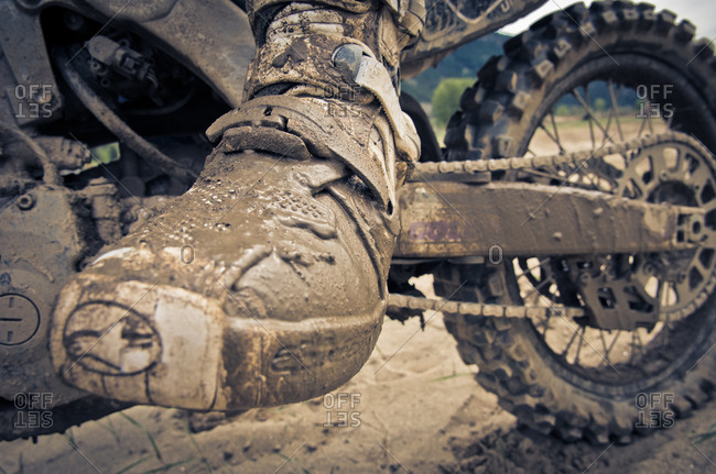 Motocross biker's muddy boot while riding