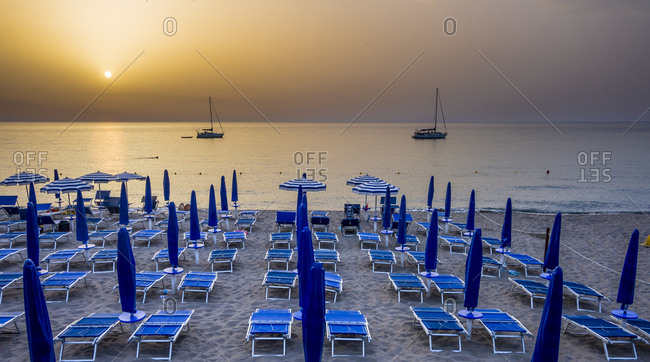 View to beach umbrellas and loungers in front of the sea at evening twilight, Cefalu, Sicily