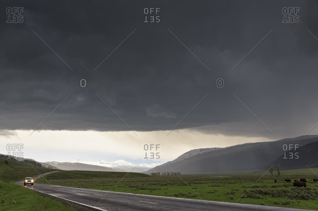 Car on Highway in stormy weather, Yellowstone National Park