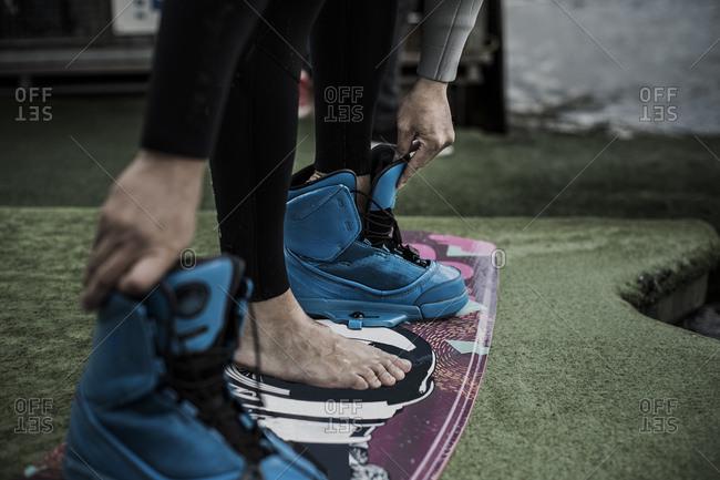 Wake boarder undressing shoes, Garbsen