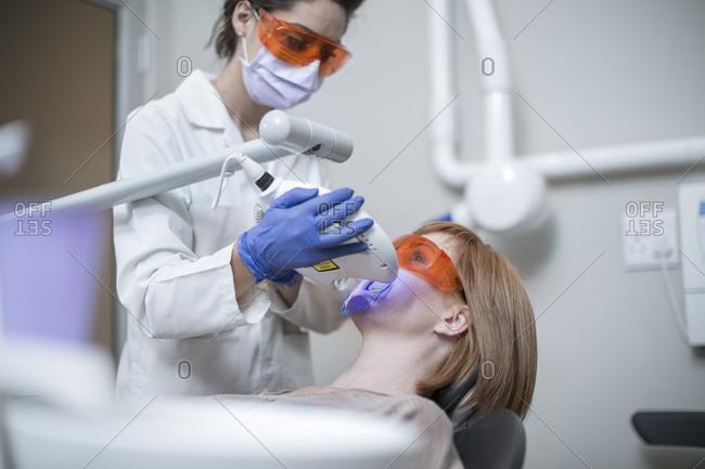 Dentist using tooth bleaching machine