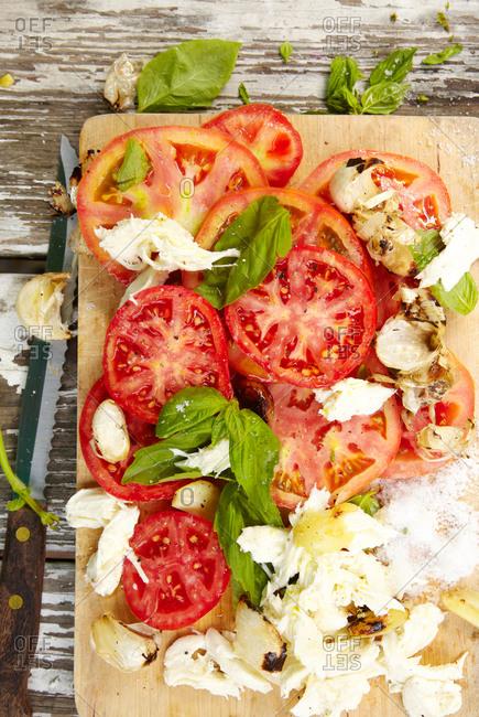 Overhead view of tomato and fresh mozzarella salad on a cutting board