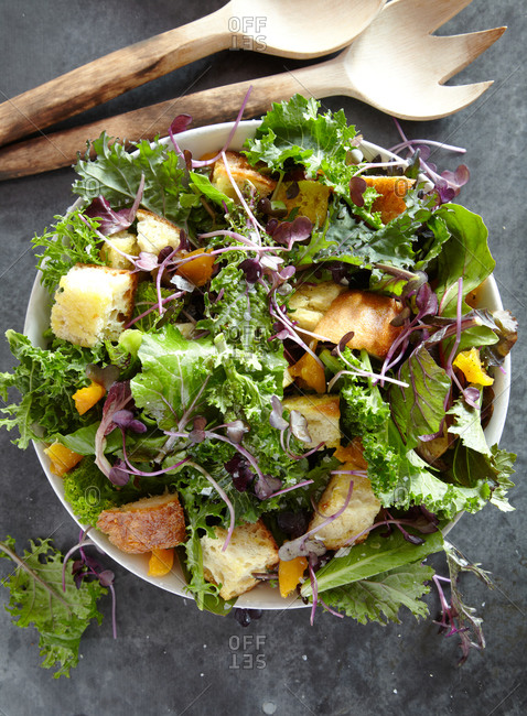 Overhead view of a green salad with croutons, pea shoots and orange sections