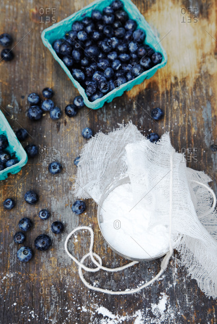 Overhead view of pints of blueberries on wooden table with sugar, string, and cheesecloth