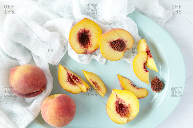 Overhead view of sliced peaches on a blue platter