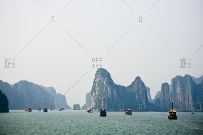 Boats travel along the waters of Halong Bay in Vietnam