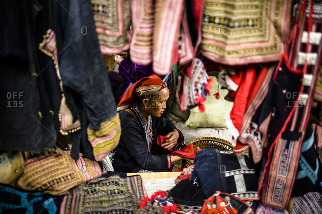 Red Dzao woman sells embroidered goods at market
