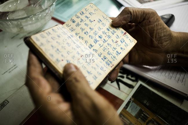 Herbalist looking through Chinese recipe book in Vietnam