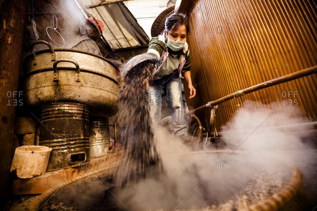 A worker steams sesame seeds at a restaurant